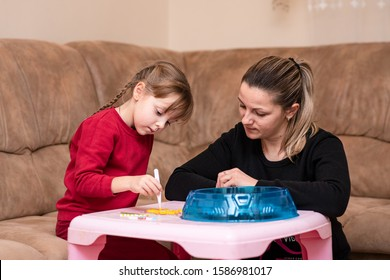 Little girl makes art toy from fusible colorful beads. Mom inspires her daughter. Game at home. Toy that develops the imagination of child, also known as perler beads.