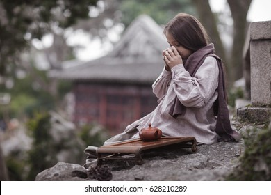 a little girl makes Chinese tea ceremony and drink tea