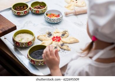 A little girl makes a dough product