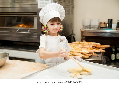 A little girl makes a flour product in a bakery