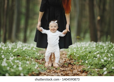 A little girl makes her first steps with mom
