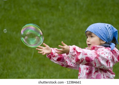 Little girl makes play with soap bubble