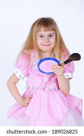 Little girl with a makeup brush and a small mirror in studio