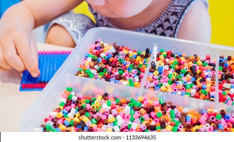 Little girl making bracelet from colorful kids beads.