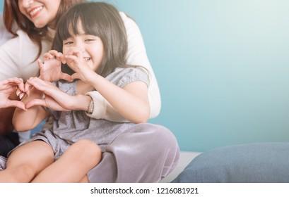 little girl making heart shape sit in mom lap.