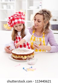 Little girl making her first fruit cake - together with her mother