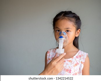 Little girl making inhalation with nebulizer at home. child asthma inhaler inhalation nebulizer steam for the treatment. Girl with flu or cold symptoms making inhalation.