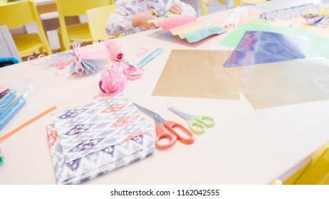 Little girl making paper butterflies from multicolor paper.