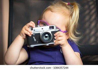 Little girl making photo with vintage camera