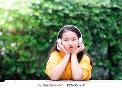 Little girl making pucker up face listening to music in the park with her headphones