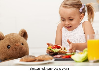 Little girl making a sandwich to her teddy bear - having a snack sitting at a table