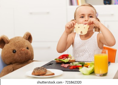 Little girl making a sandwich to her toy bear - having a healthy snack with it sitting at a small table