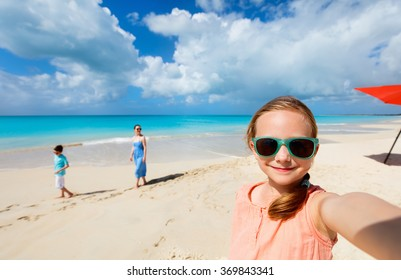 Little girl making selfie while having tropical beach vacation with her family