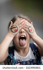 Little girl making silly face with cartoon eyes drawn on her hands.