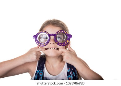 Little girl making silly face with colorful toy glasses.