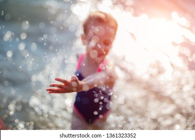 Little girl making a splash while being in the sea water soaking wet