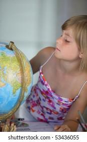 A little girl making turn a globe