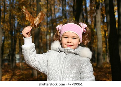 Little girl with maple leaves