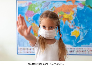 Little girl in a mask on her face. The concept of coronavirus and protection against bacteria and dirty air. The child's hand shows a stop on the background of the world map