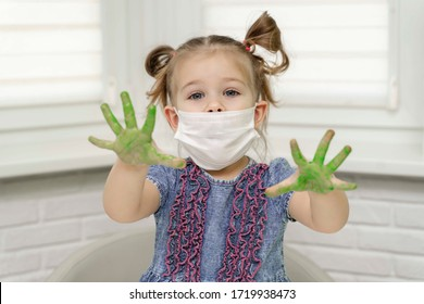Little girl in mask paints with fingers.girl shows us her green palms in paint, self-isolation, coronavirus covid-19, stay home