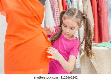 Little girl measuring  fabric on black dummy in workshop
