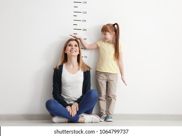 Little girl measuring height of her mother near white wall