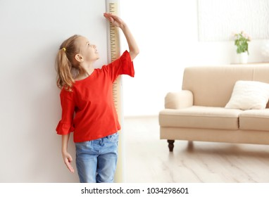 Little girl measuring height near door at home