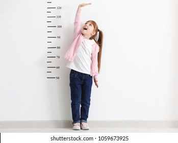 Little girl measuring height near white wall
