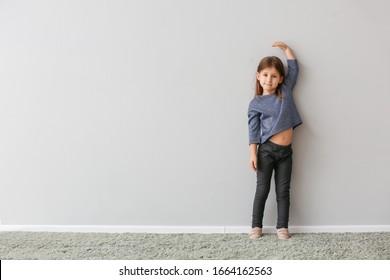Little girl measuring height near grey wall