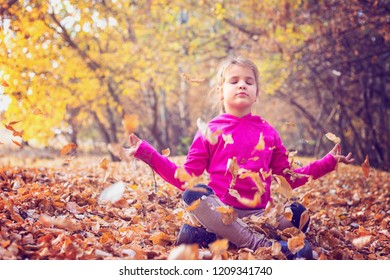 Little girl meditating and playing in the forest with autumn leaves