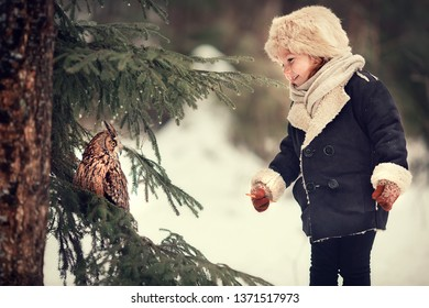 Little girl is meeting an owl in Russian forest in winter. Image with selective focus and toning