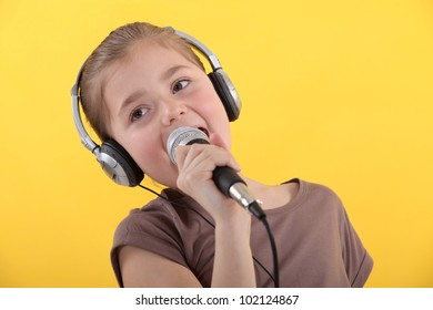 Little girl with microphone and headphones