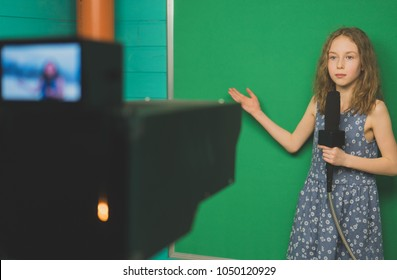Little girl with microphone standing in front of camera on green screen.