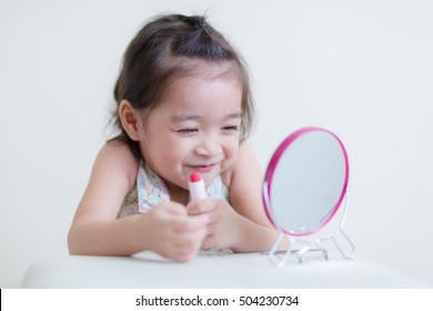 Little girl with mirror doing makeup at her house