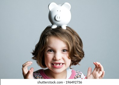 A little girl with missing teeth has a piggy bank on her head.