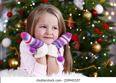 Little girl with mittens lying on fur carpet on Christmas tree background
