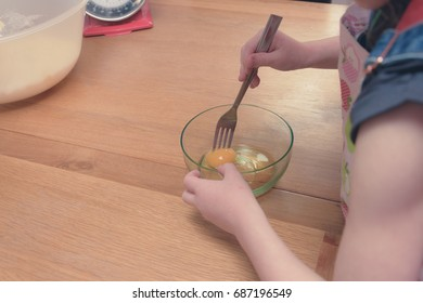little girl mixing eggs in a small glass bowl