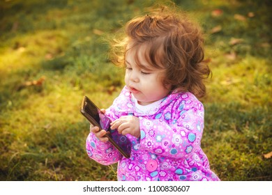 little girl with a mobile phone in the park