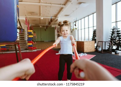 Little girl and mom doing exercises with sticks in the gym