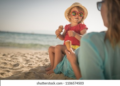 Little girl and mom on sandy beach eatin icecream