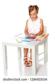 A little girl in Montessori kindergarten sits at a table and studies Montessori stuff. The concept of school and preschool education, harmonious development of the child. Isolated on white background.