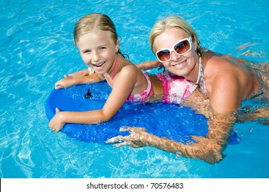 Little girl with mother boarding in blue water