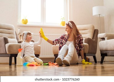 Little girl and  mother cleaning home together and having fun.