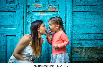 little girl with mother eating ice cream on a beautiful turquoise background of wood