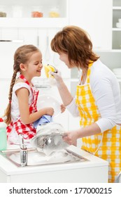 Little girl and mother having fun with the foam - washing the dishes together