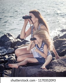 Little girl and mother looking far away with binoculars, sitting on a rock near a sea