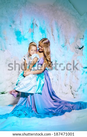 45f9c00aab897 Little girl with mother in princess dress on a background of a winter fairy  tale. Baby and mom snow queen. Smiling child and mum snowy kingdom.