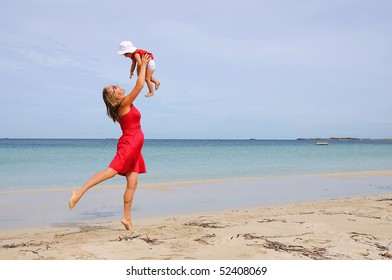 The little girl and mother in a red dress on the beach