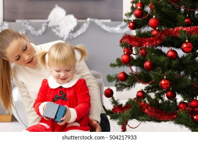 Little girl and mother sitting by christmas tree, opening presents.