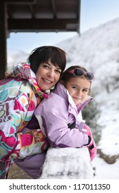 Little girl and mother at their ski cottage